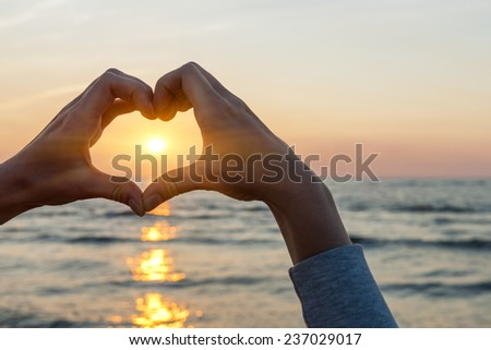 Hands and fingers in heart shape framing setting sun at sunset over ocean - stock photo