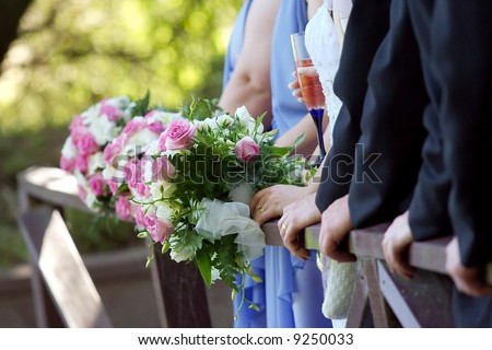 Hands and flowers of a wedding party posing for photos on a bridge. - stock photo