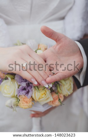 Hands and rings it is beautiful wedding bouquet - stock photo