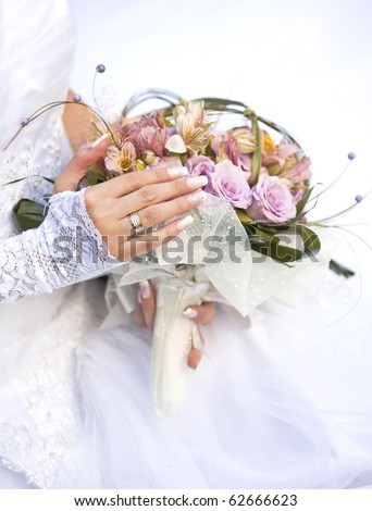 Hands and rings on wedding bouquet - stock photo