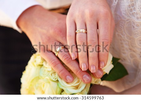 Hands and rings on wedding bouquet close up - stock photo