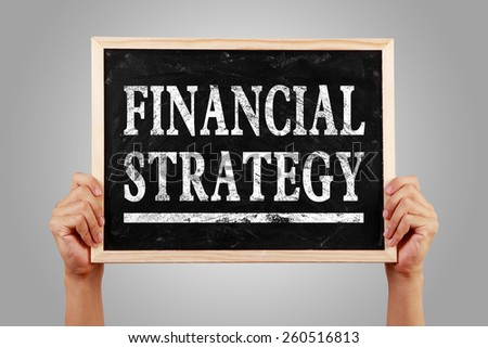 Hands are holding the blackboard of Financial strategy against gray background. - stock photo