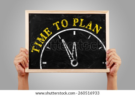 Hands are holding the blackboard of time to plan concept against gray background. - stock photo