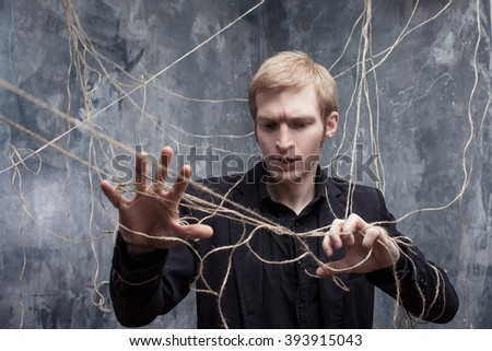 Hands are tied. Young man in  black suit got caught on the web. Concept of manipulation and slavery - stock photo