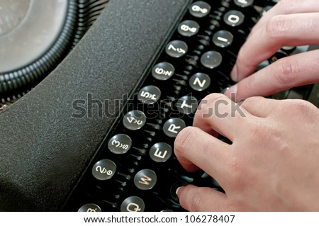 Hands are typing on vintage dirty black typewriter - stock photo