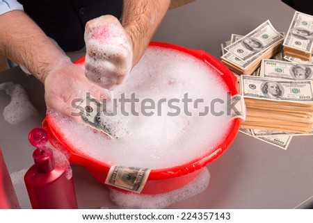 Hands are washing dollars banknotes in foam - stock photo