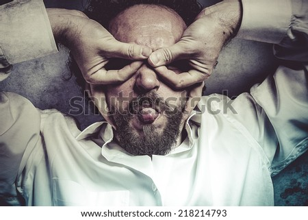 hands as a mask, man in white shirt with funny expressions - stock photo