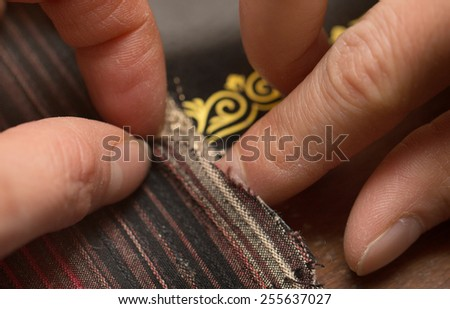 hands behind her sewing on a sewing machine - stock photo