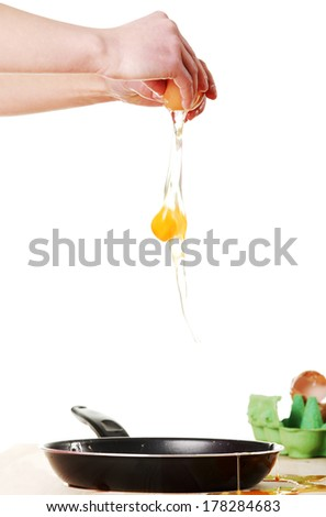Hands breaking an egg. Isolated on white background  - stock photo