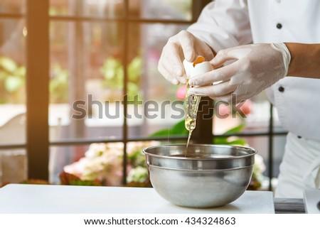 Hands breaking an egg. Raw egg pours into bowl. Key ingredient for tasty omelet. Fresh chicken egg. - stock photo