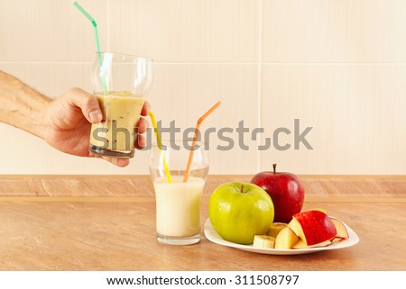Hands chef offers a fruity smoothie in glasses - stock photo