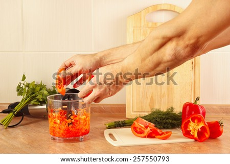 Hands chefs put chopped tomato in a blender - stock photo