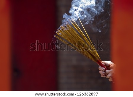 Hands clutching lit incense sticks in a Temple in Ho Chi Minh City, Vietnam. - stock photo