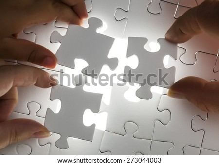 Hands completing a puzzle Jigsaw and puzzles concepts - stock photo