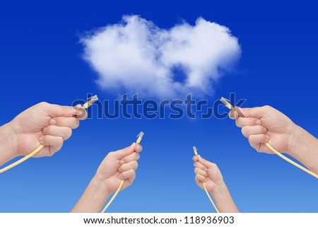 Hands connecting ethernet cable to the cloud - stock photo