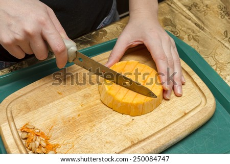Hands cook with a knife and a pumpkin. - stock photo