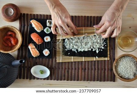 hands cooking sushi with rice, salmon and nori - stock photo