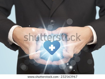 Hands creating a form with shining heart and cross in the center - stock photo