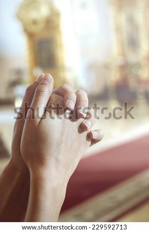 Hands crossed in prayer - stock photo