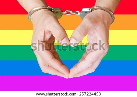hands cuffed and gay flag in the background - stock photo