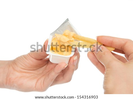 Hands dip french fries chips into cheese sauce on a white background - stock photo