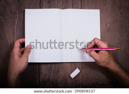 hands drawing hand writing  in notebook on wood  table,hand writing in notebook,Book,hand,Eraser,Pencil hand writing on blank paper on wood table with notebooks on wood table  - stock photo