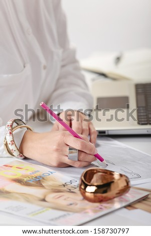 Hands drawing with pink pencil./  Close up of a hand's woman doing fashion sketches. - stock photo