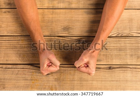 Hands emotional man close up, fists on wooden table - stock photo
