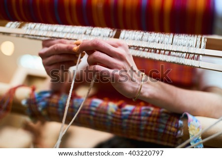 Hands engaged in production of handicraft textiles on the loom - stock photo