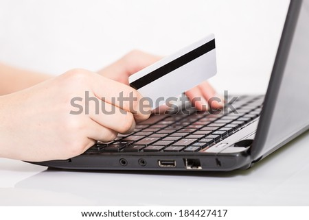 Hands entering credit card information into a laptop - stock photo
