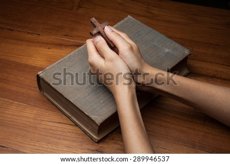 Hands folded in prayer over Holy Bible - stock photo