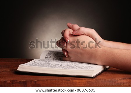 Hands folded in prayer over open russian Holy Bible on black background - stock photo