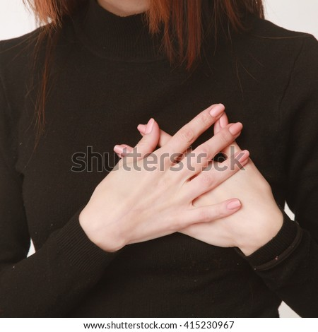 hands folded on the chest as a symbol of hard feelings (Body language, gestures, psychology) - stock photo