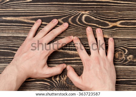 hands forming a heart on wooden background - stock photo