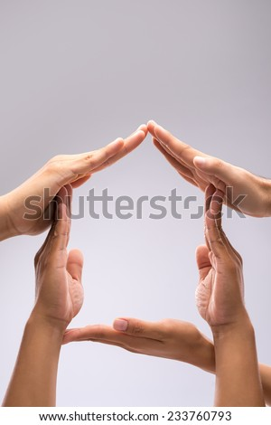 Hands forming shape of a house, isolated on gray - stock photo