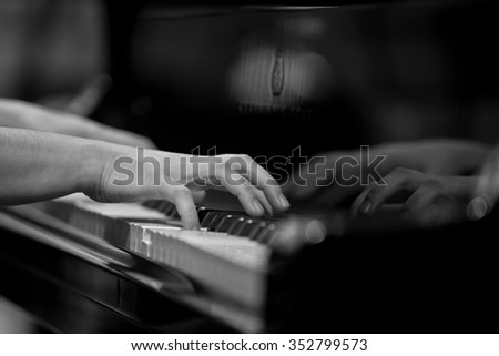 Hands girl playing the piano close-up in black and white - stock photo