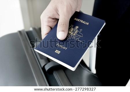Hands giving passport (of Australia) - dark tone - stock photo