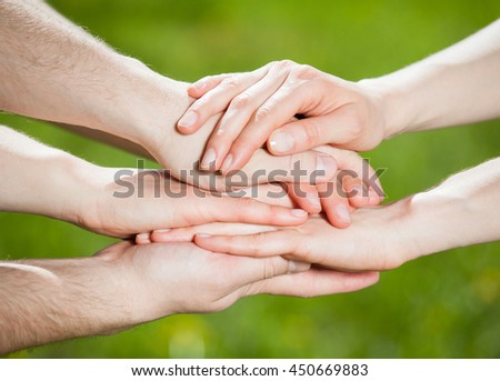 Hands group on natural green background - stock photo