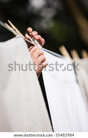 Hands hanging laundry on a clothesline outside - stock photo