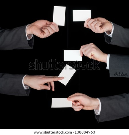 Hands hold business cards collage on black background - stock photo