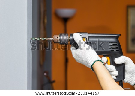 hands hold electric drill in room , interior design and home renovation DIY concept - stock photo
