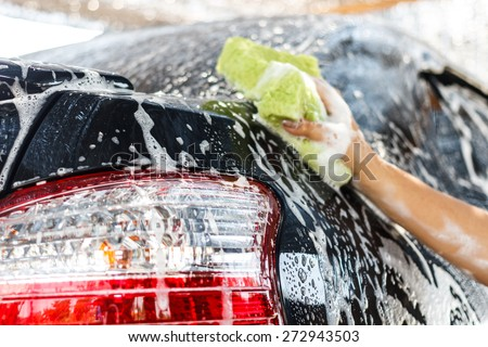 hands hold sponge for washing car - stock photo