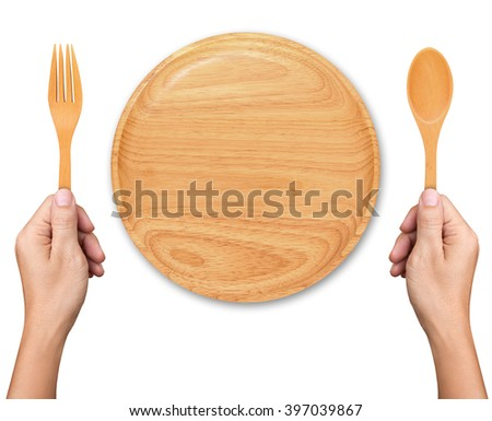Hands hold spoon and fork with Empty wood plate on white background - stock photo