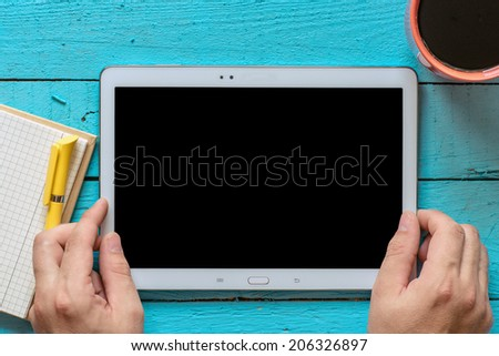 Hands hold tablet PC on wooden background - stock photo