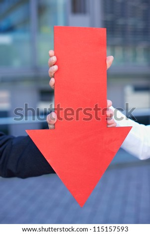 Hands holding a bold red arrow pointing down - stock photo