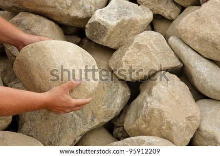 Hands holding a boulder to show scale of rocks - stock photo