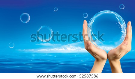 Hands holding a bubble with splashes inside against an ocean background - stock photo