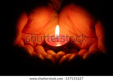 hands holding a burning candle in dark - stock photo