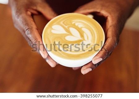 Hands holding a cappucino with heart patterns - stock photo