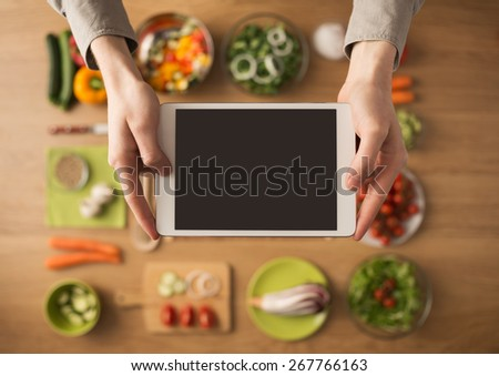 Hands holding a digital touch screen tablet with fresh vegetables and kitchen utensils on background, top view - stock photo